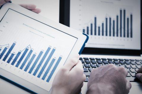 Detalhe de duas pessoas analisando gráficos no tablet e no computador